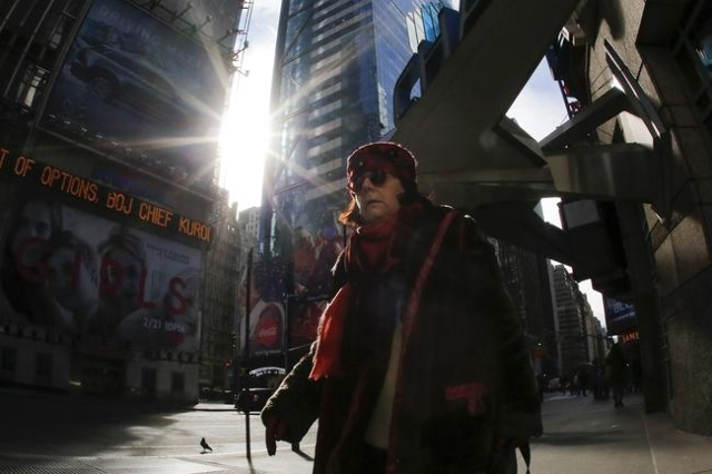 A woman is seen bundled up from the cold in Times Square, NewYork February 12, 2016. The National Weather Service says a cold front sweeping across the Great Lakes could usher in temperatures as m ...