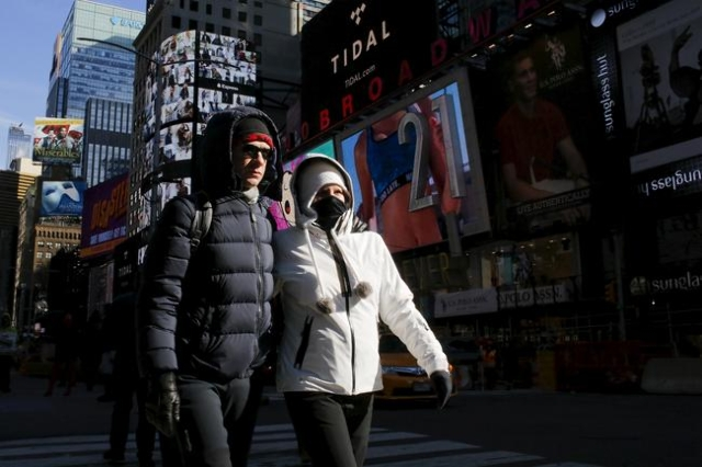 People are seen bundled up from the cold in Times Square, NewYork February 12, 2016. The National Weather Service says a cold front sweeping across the Great Lakes could usher in temperatures as m ...