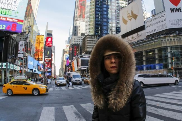 A woman is seen bundled up from the cold in Times Square, NewYork February 12, 2016.  REUTERS/Eduardo Munoz