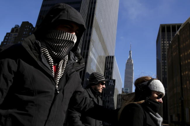 People walk down 8th avenue in New York February 13, 2016. REUTERS/Andrew Kelly