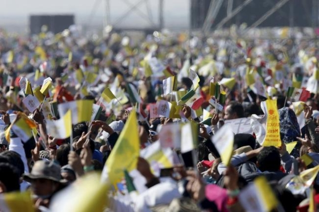 People wave flags as the helicopter carrying Pope Francis flies over the area where the pope will celebrate Mass before before a crowd of hundreds of thousands in Ecatepec, Mexico, February 14, 20 ...
