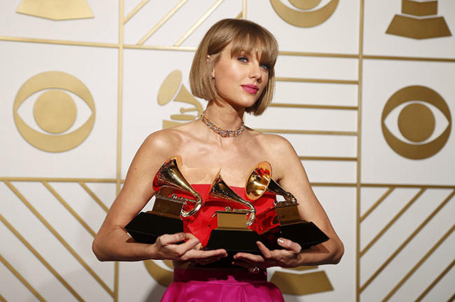 """Singer Taylor Swift poses backstage with her awards for Best Music Video for """"Bad Blood"""", Album of the Year and Best Pop Vocal Album for """"1989"""" during the 58th Grammy Awards in ..."""