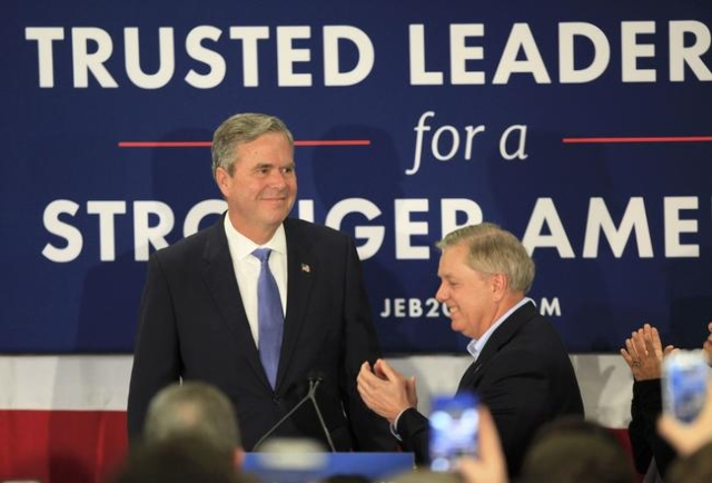 Jeb Bush (L) is applauded by U.S. Senator Lindsey Graham (R) as he arrives to announce that he is ending his campaign for the White House by suspending his campaign for the Republican presidential ...