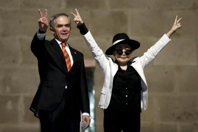 Artist Yoko Ono (R) and Mexico City's mayor Miguel Angel Mancera gesture after she was honored as 'Illustrious Visitor' at Mexico City's town hall in this Mexico City, Febr ...