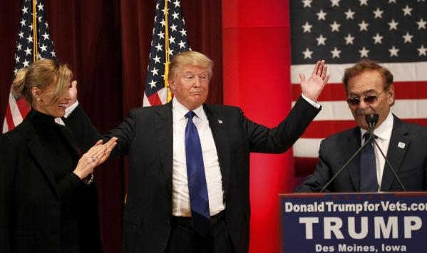 Republican U.S. presidential candidate Donald Trump (C) reacts to Las Vegas billionaire Phil Ruffin (R), owner of the Treasure Island Casino, pledging a $1-million donation to U.S. veterans as he  ...