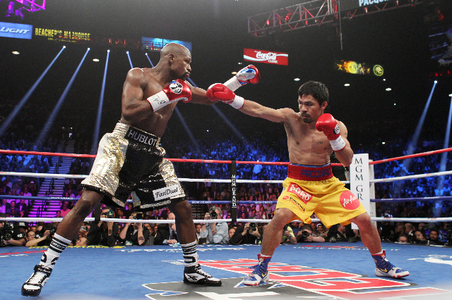 Floyd Mayweather Jr. and Manny Pacquiao feel each other out early in their welterweight unification boxing match at the MGM Grand Garden Arena in Las Vegas on Saturday, May 2, 2015. (Sam Morris/La ...
