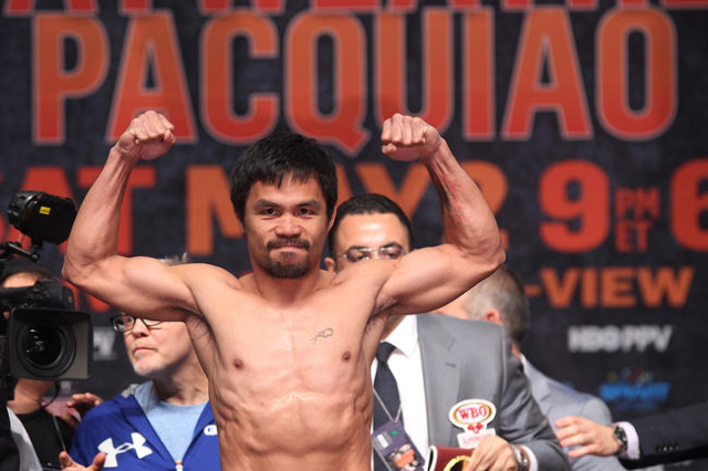 Manny Pacquiao flexes after making weight during the weigh in for his welterweight unification fight against Floyd Mayweather Jr. Friday, May 1, 2015, at the MGM Grand Garden Arena. (Sam Morris/La ...