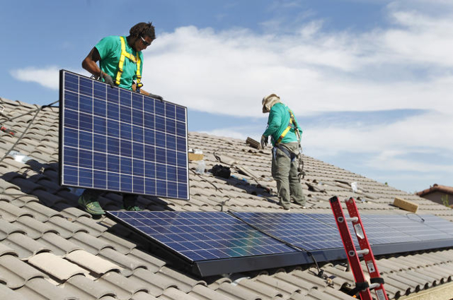 Solar City installation crew leader Greg Kates, left, and Guillermo Aviles install solar panels on a North Las Vegas home Thursday, Oct. 30, 2014. (Las Vegas Review-Journal)