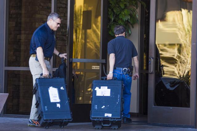 Law enforcement personnel enter a building at 8880 Sunset Road on Thursday, Feb. 18, 2016. (Jeff Scheid/Las Vegas Review-Journal Follow @jlscheid)