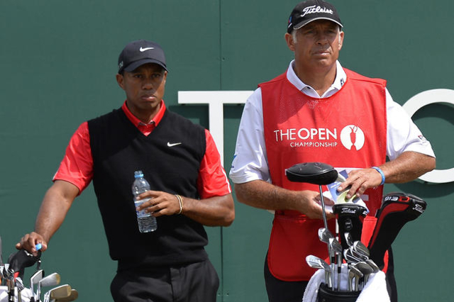 Tiger Woods of the U.S. (L) stands behind his former caddie Steve Williams at the start of his final round of the British Open golf Championship at Muirfield in Scotland July 21, 2013. (Russell Ch ...