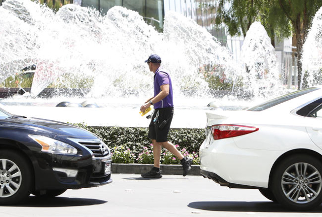 A valet parking attendant runs past the fountain at the Aria hotel-casino on the Las Vegas strip,  June 19, 2015.  (Bizuayehu Tesfaye/Las Vegas Review-Journal Follow @bizutesfaye)