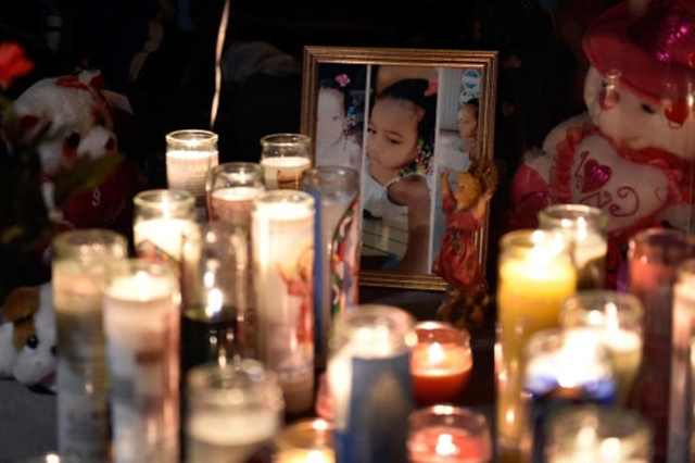 Candles illuminate a framed photograph of 2-year-old Evelyn Green during a candlelight vigil along Thomas Avenue Monday, Feb. 8, 2016, in North Las Vegas. Green was killed in a hit and run acciden ...