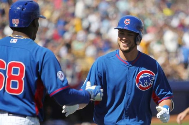 Kris Bryant is congratulated after hitting a solo home run in the sixth inning against the Oakland Athletics in their Major League Baseball game at Cashman Field in Las Vegas Sunday, March 14, 201 ...