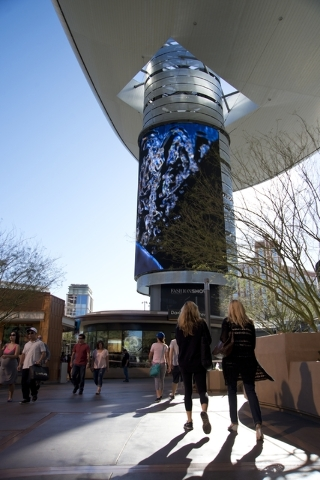 "Visitors walk toward one of the massive screens recently added to the pillars underneath the ""Cloud,"" a steel canopy at the Fashion Show Mall on the Las Vegas Strip on Thursday,  ..."