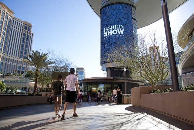 """Visitors walk toward one of the massive screens recently added to the pillars underneath the """"Cloud,"""" a steel canopy at the Fashion Show Mall on the Las Vegas Strip on Thursday,  ..."""