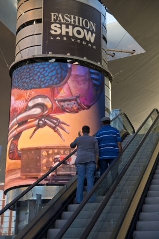 "Visitors ascend an escalator near one of the massive screens recently added to the pillars underneath the ""Cloud,"" a steel canopy at the Fashion Show Mall on the Las Vegas Strip  ..."