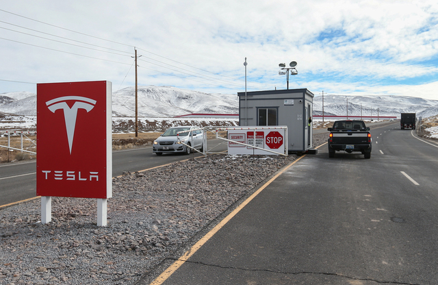 Traffic moves past the main gate of the Tesla gigafactory in the Tahoe-Reno Industrial Center, east of Sparks, Nev. on Wednesday, Feb. 3, 2016. The approximately 10 million square foot lithium-ion ...