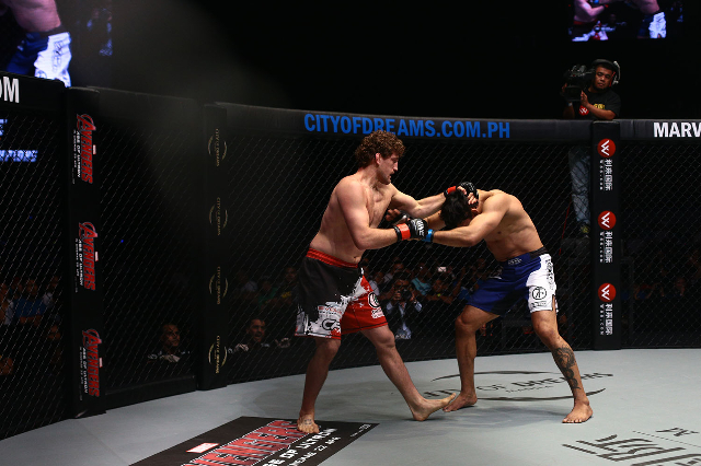 ONE Championship welterweight champion Ben Askren, left, locks up with Luis Santos on April 24 in Pasay, Philippines. The bout ended in a no-contest when Santos couldn't continue after an ey ...