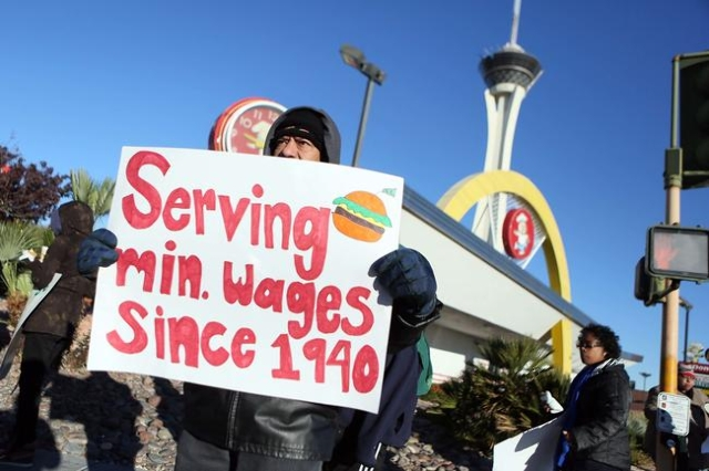 Cesar Torres holds a sign during a protest outside McDonald's on 2248 Paradise Road Thursday, Dec. 5, 2013, in Las Vegas. Community members and fast-food workers gathered as part of a nation-wid ...