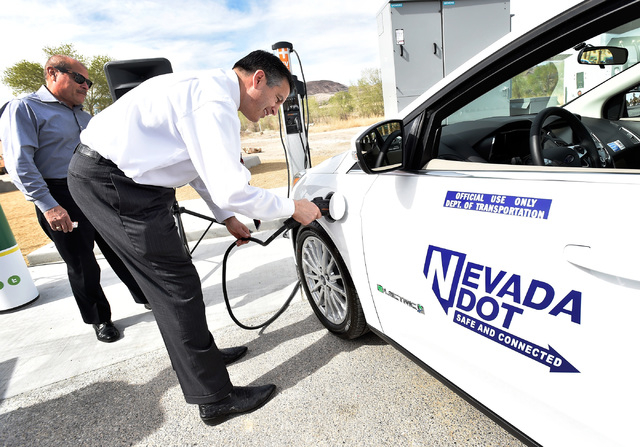 Gov. Brian Sandoval plugs in an all-electric vehicle after arriving at the dedication of the first electric car charging station along U.S. Highway 95 on Tuesday in Beatty. The station is the fist ...