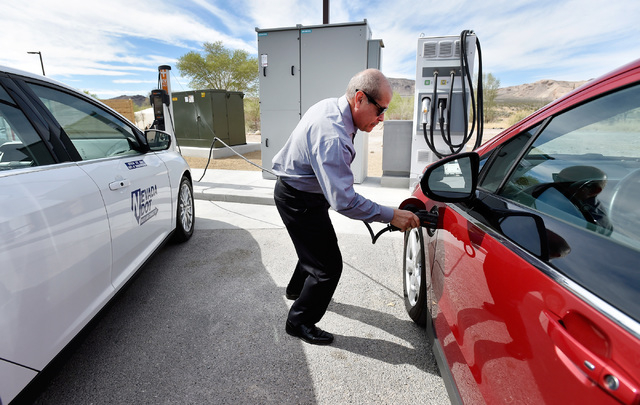 Rudy Garcia plugs-in an all-electric vehicle at the dedication of the first electric car charging station along U.S. Highway 95 Tuesday, March 1, 2016, in Beatty. The station is the fist of many p ...