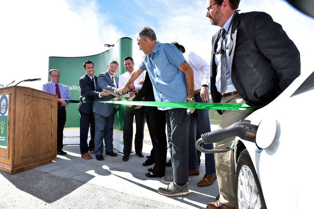 Nevada Gov. Brian Sandoval, center, with other dignitaries cut a ribbon to dedicate the first electric car charging station along U.S. Highway 95 Tuesday, March 1, 2016, in Beatty. The station is  ...