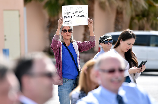 Laura Cunningham of Beatty, displays a sign during the dedication of a the first electric car charging station along U.S. Highway 95 on Tuesday, March 1, 2016, in Beatty. The station is the fist o ...