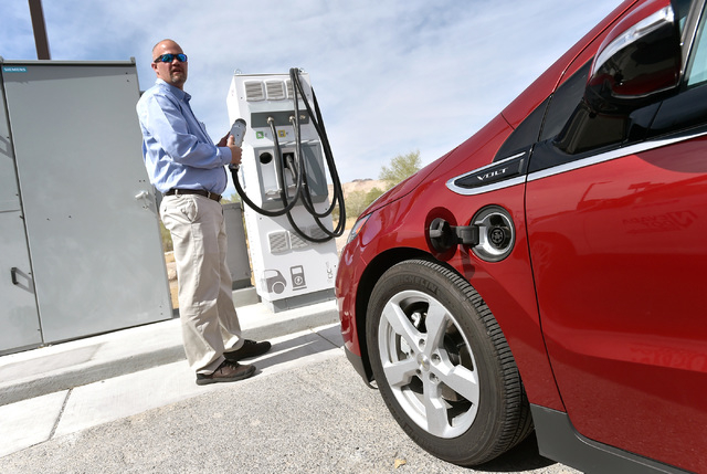 Craig Swan looks to plug in a Chevrolet Volt during the dedication of a the first electric car charging station along U.S. Highway 95 on Tuesday, March 1, 2016, in Beatty. The station is the fist  ...