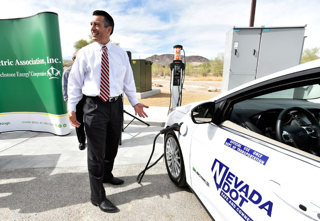 Nevada Gov. Brian Sandoval reacts to how easy it was to plug-in an all-electric vehicle after arriving at the dedication of the first electric car charging station along U.S. Highway 95 Tuesday, M ...
