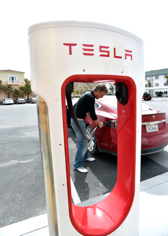 Wild Hominoid goes to unplug his Tesla electric car near the dedication of a the first electric car charging station along U.S. Highway 95 on Tuesday, March 1, 2016, in Beatty. The station is the  ...