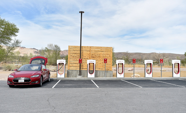 A Tesla electric car is seen charging before the dedication first electric car charging station along U.S. Highway 95 Tuesday, March 1, 2016, in Beatty. The station is the fist of many planned cha ...