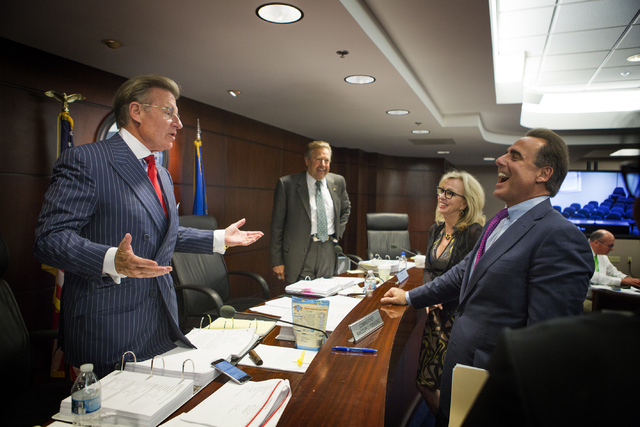 Caesars Entertainment President and CEO Mark Frissora, right, laughs while talking to Nevada Gaming Commissioner Randolph Townsend after he was approved for license by the Nevada Gaming Commission ...