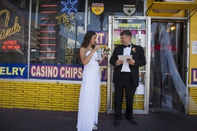 Zarema Zinnurova, left, and Sergiu Opinca stand in the shade of an antique shop after getting married at the nearby Graceland Wedding Chapel, 619 S. Las Vegas Blvd., on Tuesday, July 21, 2015, in  ...