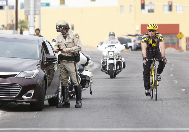 A Metro police officer talks to a driver of a car that was pulled over for failure to provide 3 feet between the vehicle and a decoy bicyclist, right, he passed during Bicyclist Safety Campaign on ...