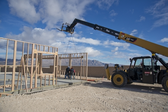 Workers put together the wood frame of a home inside the Teton Cliffs subdivision of the Skye Canyon master-planned community off U.S. Highway 95 at Skye Canyon Drive in northwest Las Vegas on Mon ...