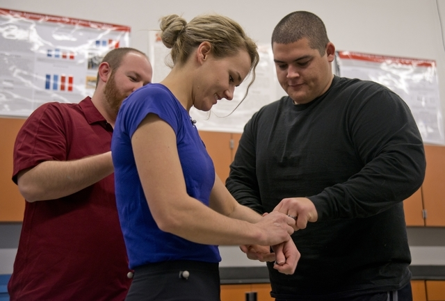 Jeff Eggleston, left, and John Harry adjust reflective balls on Sophia Bradley in order to track her with a 10-camera motion capture system inside the Sports Injury Research Center in the Paul McD ...
