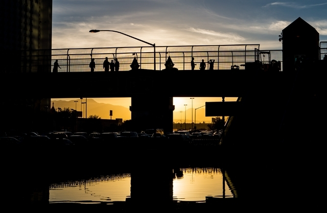 Pedestrians, silhouetted against the sunset, cross a pedestrian bridge over Tropicana Avenue at Las Vegas Boulevard Feb. 11. Chase Stevens/Las Vegas Review-Journal