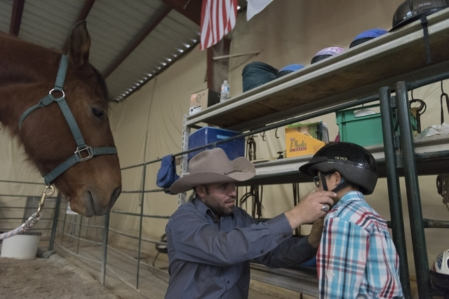 Paul Rogers, co-owner of Paradise Ranch, puts a helmet on eight-year-old Diego Diaz prior to Diaz's horse-assisted therapy session at the ranch at 1722 Primrose Path in Las Vegas Saturday, Feb. 13 ...