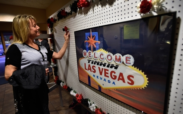 Linda Dressel adds a carnation bloom to a wall of flowers that represents a person who is fighting addiction, overcame addiction or was lost to addiction during There is No Hero in Heroin Foundati ...