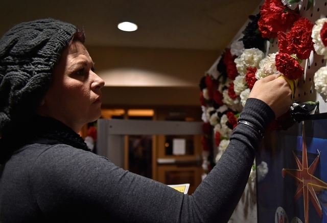 Debbie Hagen adds a carnation bloom to a wall of flowers that represents a person who is fighting addiction, overcame addiction or was lost to addiction during There is No Hero in Heroin Foundatio ...
