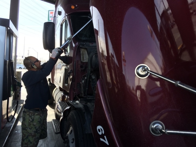 Juan Santos cleans the windowshield of his 500 Hp tractor-trailer March 15, 2016, at a Las Vegas truck stop. He drives interstate routes and said being tired is part of the job as he often works 1 ...