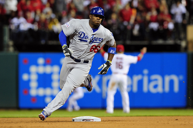 Oct 6, 2014; St. Louis, MO, USA; Los Angeles Dodgers right fielder Yasiel Puig (66) rounds second base after hitting a triple during the sixth inning against the St. Louis Cardinals in game three  ...