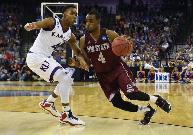Mar 20, 2015; Omaha, NE, USA; New Mexico State Aggies guard Ian Baker (4) drives to the basket against Kansas Jayhawks guard Devonte Graham (4) during the second half in the second round of the 20 ...
