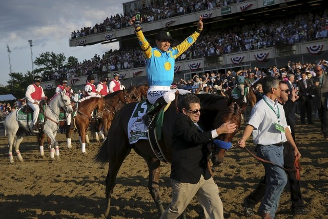 Jockey Victor Espinoza, aboard American Pharoah, celebrates after winning the 147th running of the Belmont Stakes as well as the Triple Crown, in Elmont, New York June 6, 2015.  (Lucas Jackson/Reu ...