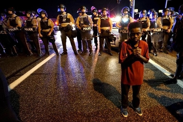 Amarion Allen, 11-years-old, stands in front of a police line shortly before shots were fired in a police-officer involved shooting in Ferguson, Missouri August 9, 2015.   (REUTERS/Rick Wilking)