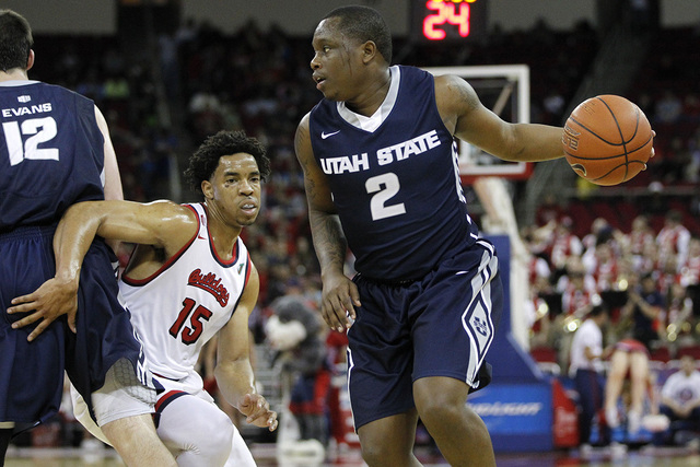 Feb 20, 2016; Fresno, CA, USA; Utah State Aggies guard Darius Perkins (2) dribbles the ball as Fresno State Bulldogs guard Lionel Ellison III (15) defends in the first half at the Save Mart Center ...