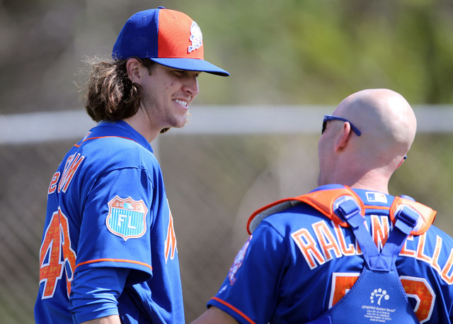 Feb 22, 2016; Port St. Lucie, FL, USA; New York Mets starting pitcher Jacob deGrom (left) talks with Mets bullpen catcher Dave Racaniello (right) during spring training work out drills at Traditio ...
