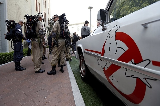 "Enthusiasts wearing Ghostbusters costumes stand by an ECTO-1, the vehicle used in the upcoming movie ""Ghostbusters,"" during a photo call at Sony Studios in Culver City, California March 2, 2016.   ..."