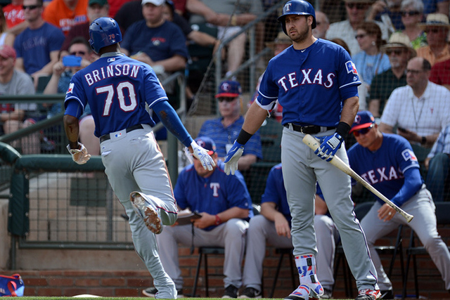 Mar 3, 2016; Surprise, AZ, USA; Texas Rangers center fielder Lewis Brinson (70) scores a run in front of Texas Rangers left fielder Joey Gallo (13) during the first inning against the Kansas City  ...