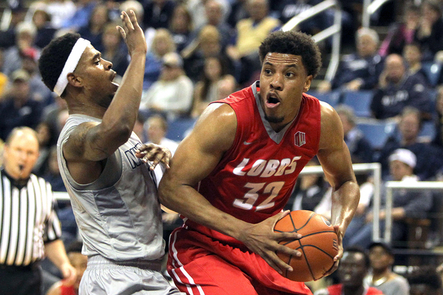 Mar 5, 2016; Reno, NV, USA; New Mexico Lobos forward Tim Williams (32) shoots in front of Nevada Wolf Pack guard Tyron Criswell (2) during the second half of their NCAA basketball game at Lawlor E ...